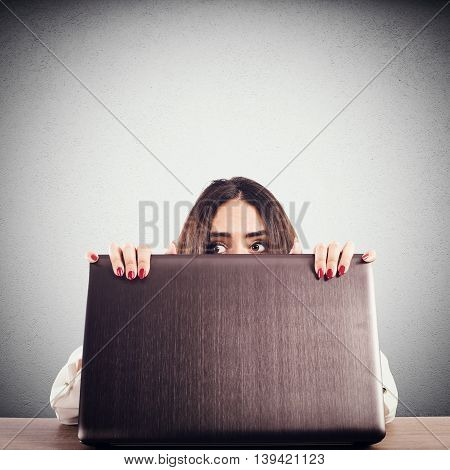 Woman hidden behind the computer screen peeks secretly