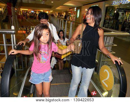 CEBU CITY, CEBU / PHILIPPINES - AUGUST 12, 2011: People ride the escalator in the SM City Cebu shopping mall.