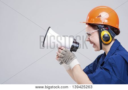 Professions Concepts.Portrait of Expressive Caucasian Female With Loudspeaker Horn Posing In Hardhat Against White. Equipped with Coverall. Horizontal Image