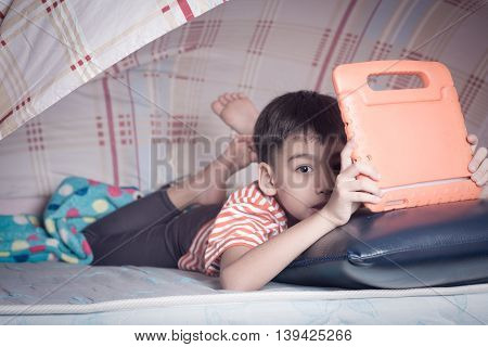 Little boy hiding under blanket playing tablet