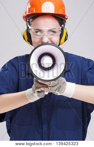 Professions Concepts and Ideas.Portrait of Expressive Caucasian Female With Loudspeaker Horn Shouting In Hardhat. Equipped with Coverall.Vertical Shot