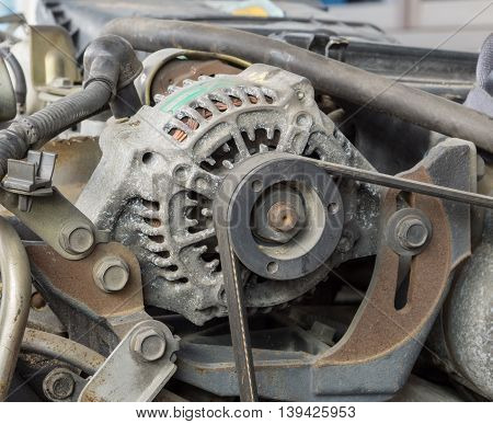 Old alternator for the car attached on engine