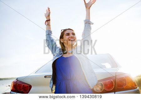 summer vacation, holidays, travel, road trip and people concept - happy smiling teenage girl or young woman near car at seaside