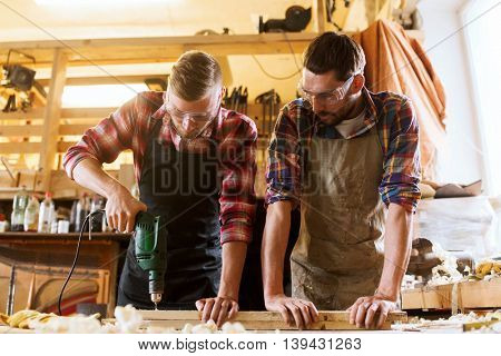 profession, carpentry, woodwork and people concept - two carpenters with electric drill drilling wood plank at workshop poster