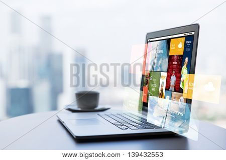 technology, internet, media, business and modern life concept- close up of open laptop computer with news web page on screen and coffee cup on table at office or hotel room