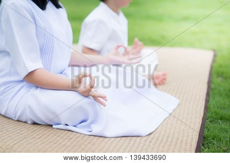 Beautiful Asian children meditating in lotus position