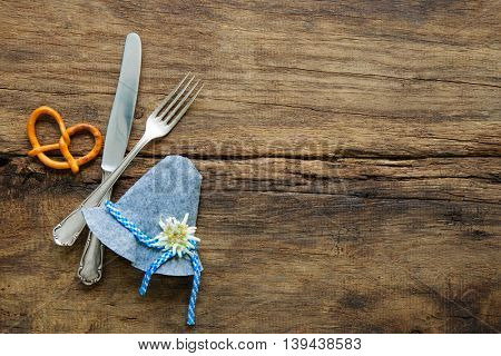 Bavarian cutlery, hut with edelweiss and pretzel on wooden table with copy space for Oktoberfest