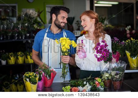 Couple holding bunch of flowers and spray bottle in the flower sho