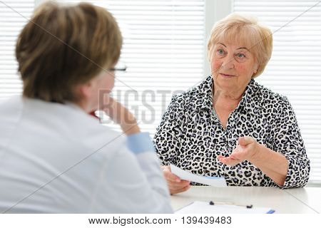 Female senior patient tells the doctor about her health complaints
