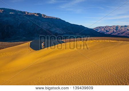 The woman with camera have difficulty climbing dune. Mesquite Flat Sand Dunes. Bright sunny morning in a picturesque part of Death Valley, USA