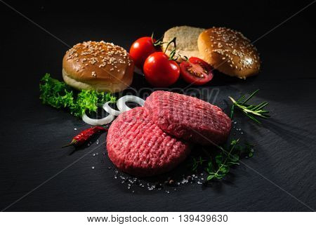 Homemade hamburger. Raw beef patties, sesame buns with other ingredients for hamburgers on dark slate plate