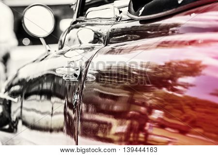 Close up photo of veteran vintage car with rear-view mirror and handle. Transition from colorless to red. Old automobile. Vibrant colors.