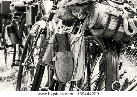 Old military bicycle with kitbag and equipments. Backpack and containers for food and drink. Vintage scene. Black and white photo. Retro transport. Equipment of german soldier in World War II.
