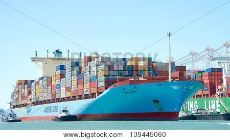 Oakland CA - July 19 2016: Cargo Ship GERDA MARSK with multiple tugboats assisting the vessel to maneuver into the Port of Oakland the fifth busiest port in the United States.