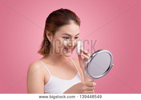 Young lady applying blusher on her face with powder puff and mirror skin care concept on pink background.