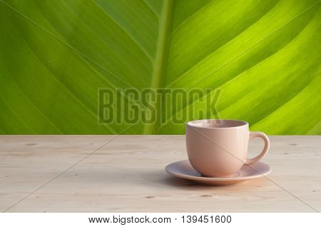 brown coffee cup on wood floors and green leaf background texture.
