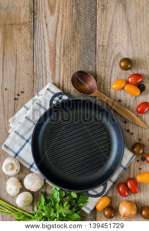 Frying pan, fresh cooking ingredients and spices ready for cooking on rustic wooden background. Healthy cooking concept with copy space. Table top view food frame