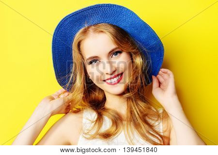 Portrait of a beautiful girl with a happy toothy smile over yellow sunny background. Summer holidays. Healthy teeth. Happiness.
