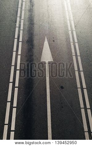 high point of view on a multi lane asphalt road with a white arrow for straight through traffic