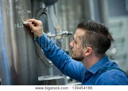 Attentive maintained worker writing on tank at brewery