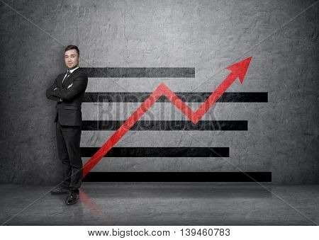Full portrait of a young businessman with his arms crossed isolated on a concrete background with an increasing graph. Business presentation. Financial chart. Succesful management.
