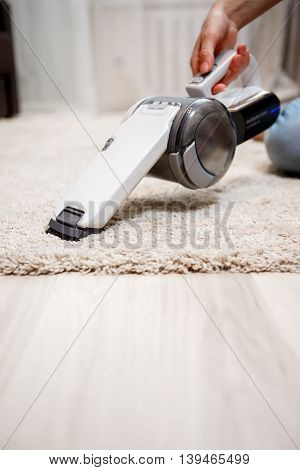 Female hand holding small white cordless vacuum cleaner and cleaning rug indoors