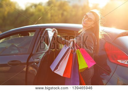 Smiling Caucasian woman putting her shopping bags into the car - Let's go shopping concept