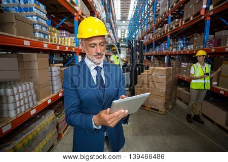 Focus of manager is using a tablet and wearing a hard hat in a warehouse