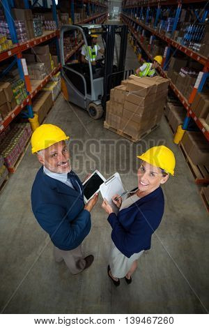 High angle view of managers are wearing hard hat and looking the camera in a warehouse