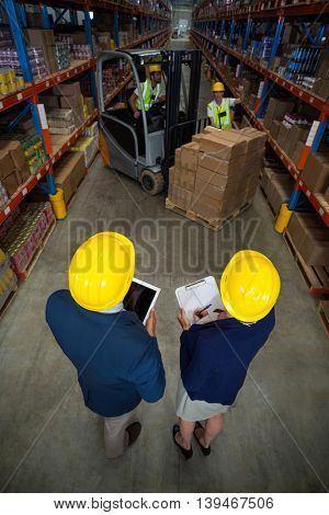 High angle view of manager wearing hard hat and looking workers in a warehouse