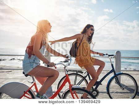 Two Friends Out For A Bike Ride On Seaside Promenade