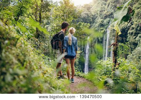 Couple Of Hikers Viewing Waterfall