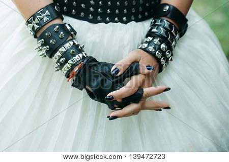 Female hands in black leather glove and bracelets with thorns and rivets in gothic punk style on white skirt background