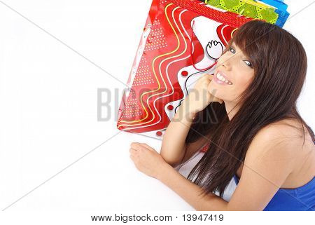 Closeup of young attractive girl smiling on surprise in the colorful shopping bags