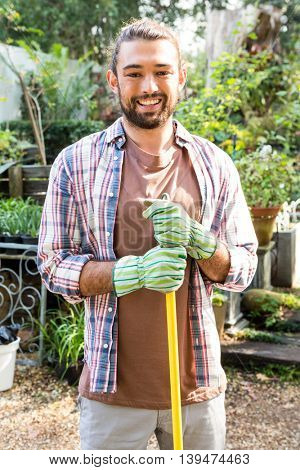 Portrait of young hipster gardener with tool at community garden