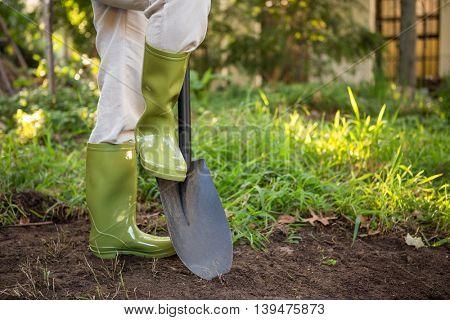Low section of female gardener standing with shovel at community garden