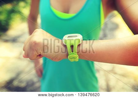 young woman jogger ready to run set and looking at sports smart watch checking performance or heart rate pulse trace. Sport and fitness outdoors on forest trail.