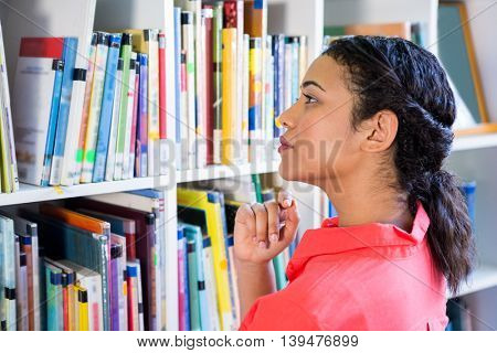 Young teacher searching book from bookshelf at school library