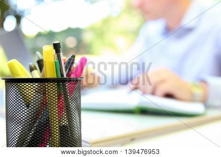 businessman working with a laptop sitting outside. Pen pensils ahead