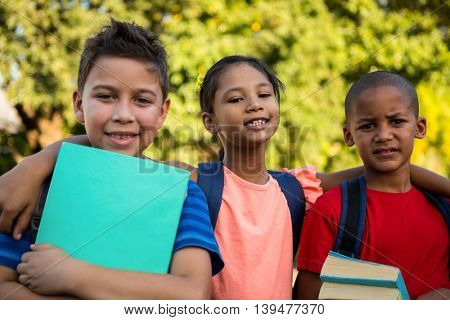 Portrait of classmates with arms around at school campus