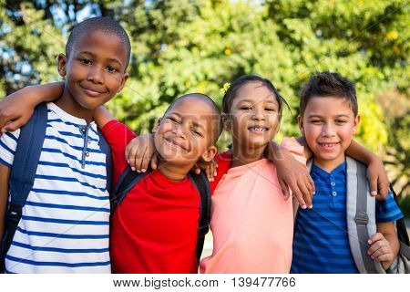 Portrait of smiling classmates with arms around at school campus