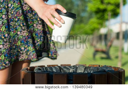 Close-up Female Hand Throwing Paper Cup On Trash