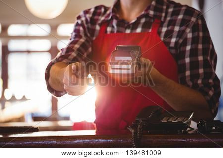 Mid section of waiter showing credit card machine at café