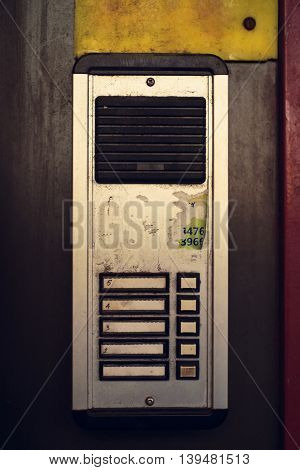 A grimy apartment intercom in New York City.