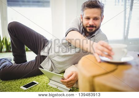 Young businessman taking coffee cup while relaxing at creative office