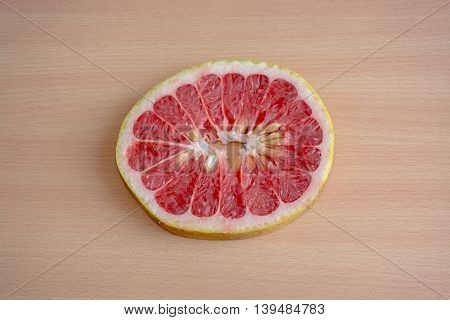 A Slice Of Red Pomelo On A Wooden Background