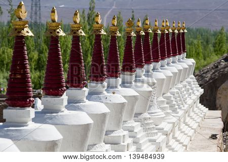 Buddhist chortens white stupa and Himalayas mountains in the background near Shey Palace in Ladakh India