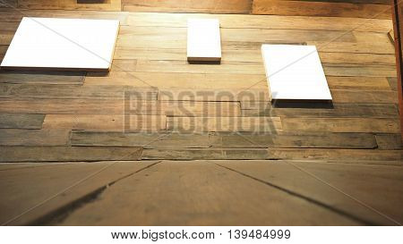 Picture canvas white color frame on wall and floor perspective antique Red Balau wood macro photo Right corner is blur concept antique coffee shop background.