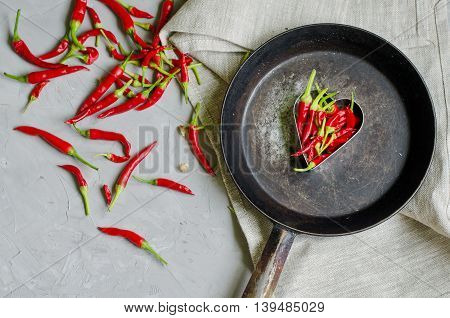 Little chilly peppers in a heart shape on an iron frying pan on gray background concept of hot love and passion