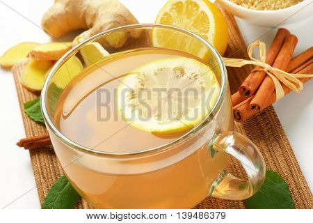 close up of cup of ginger tea with lemon, fresh ginger and cinnamon on wooden cutting board